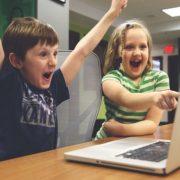 子供達がパソコンで放送されているサッカーの試合を見て喜んでいる