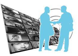 数々の液晶画面の前で交渉が成立している場面