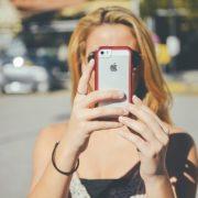 スマホを顔の前に持ってきて写真をとっている女性