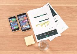 レポート資料とiphoneとメモ用紙とグラスが机の上に置かれている