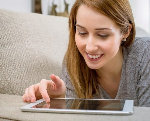 ソファーで横になりながら笑顔でiPadを操作している女性