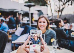 レストランのテラス席で友達に写真を撮られている女性