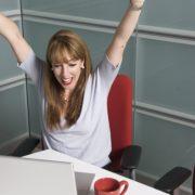 パソコンでの作業が終わりやったーと喜んでいる女性