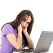 女性がパソコンを見ながら悩んでいる